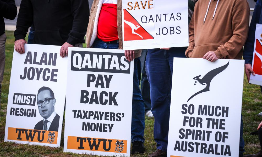 Protesters hold placards as they attend a rally at Parliament House on 3 September 2020 in Canberra.