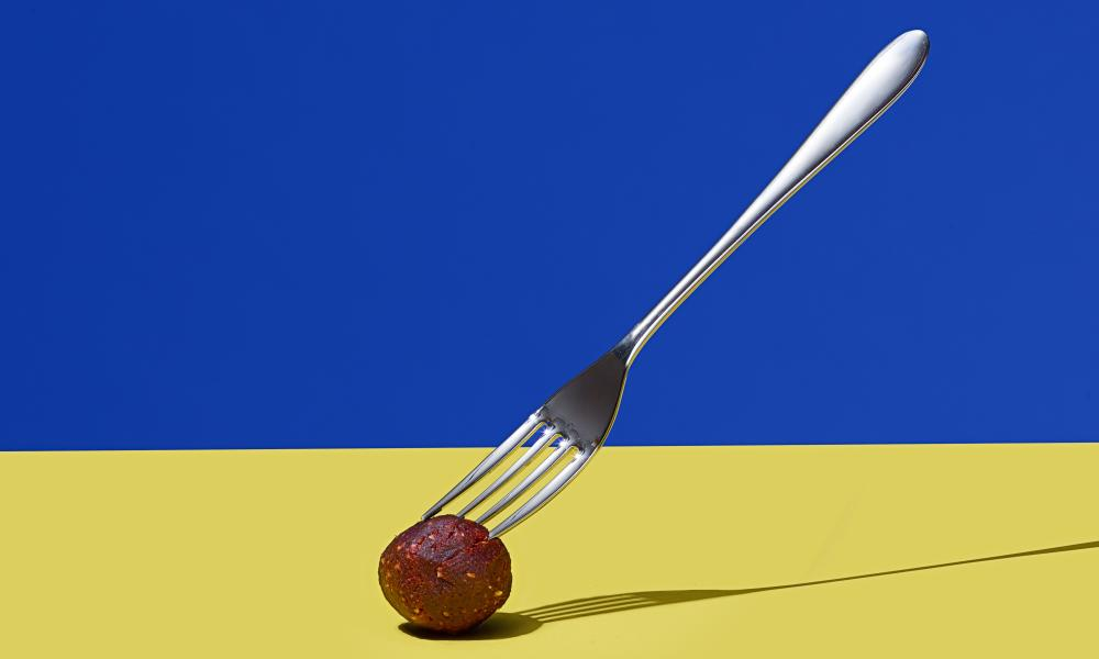 Protein ball on yellow surface, speared by fork against blue background