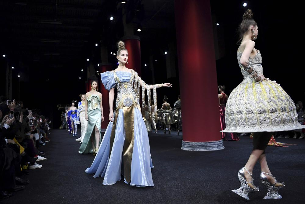 Models present creations by Guo Pei