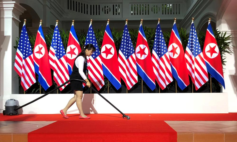 A worker vacuums the spot where Donald Trump and Kim Jong-un are expected to shake hands