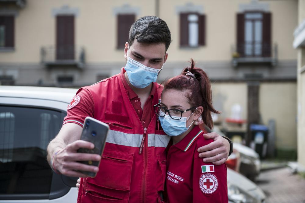 Red Cross staff take a selfie at the Red Cross headquarters in Turin