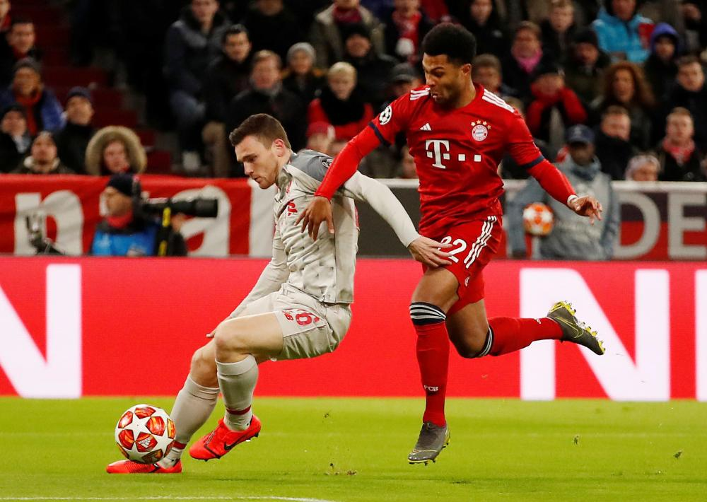 Robertson holds off Gnabry.