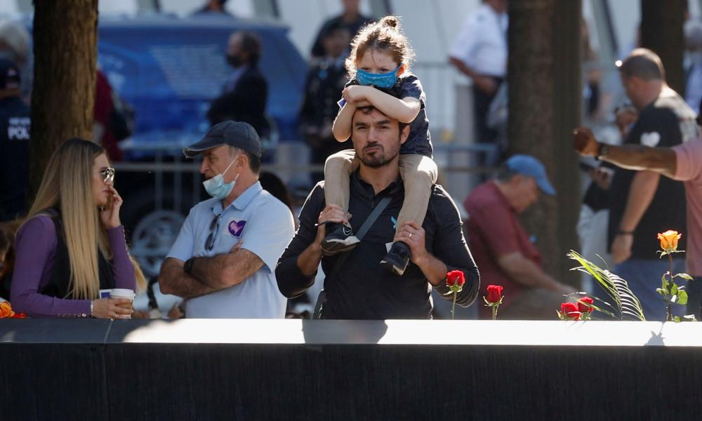 A man with his daughter on his shoulders looks on at the north reflecting pool of the 9/11 Memorial on the 20th anniversary of the September 11 attacks in Manhattan, New York City.