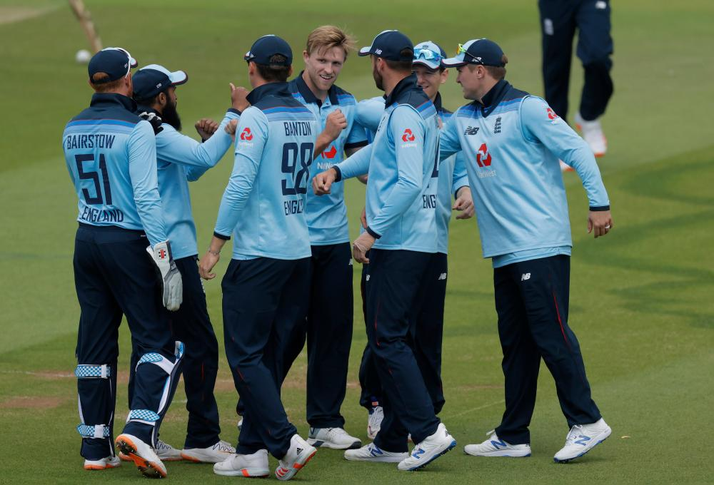 David Willey celebrates with England teammates after Tom Banton caught Paul Stirling off his bowling.