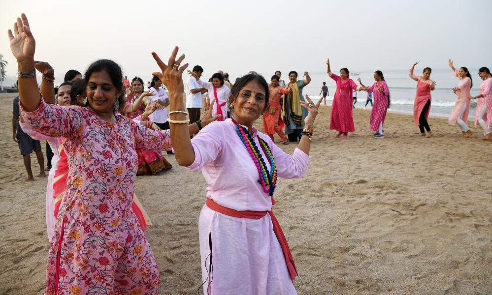 Women wearing pink dresses perform Garba dance on Juhu beach in Mumbai.
