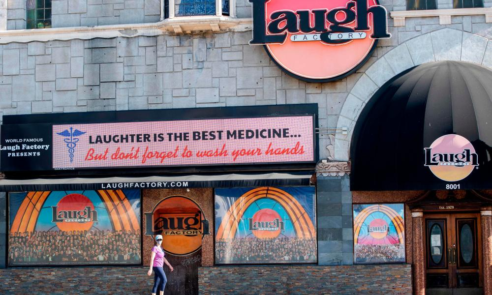 Awoman walks past the Laugh Factory comedy club, closed amid the coronavirus pandemic on the Sunset Strip in West Hollywood, California.
