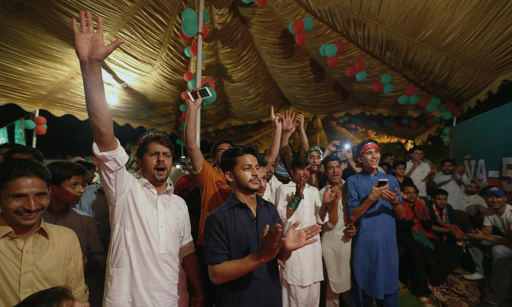 Imran Khan supporters watch preliminary results come in on television.