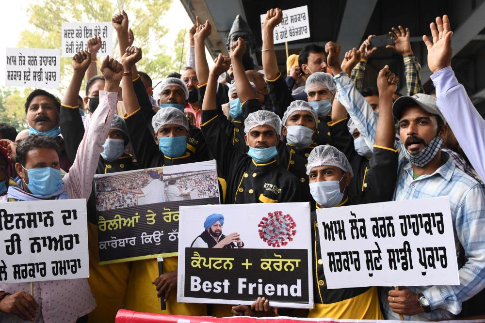 Owners and workers from the food and hotel service industry protest in Amritsar on Monday against a night curfew imposed by the state government.