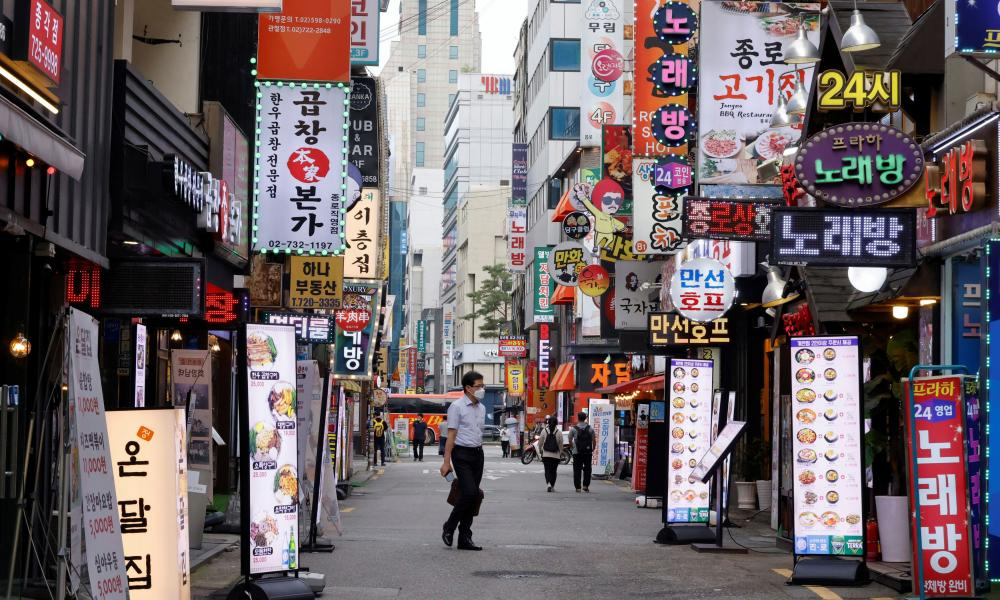 A man walks on a nearly empty street amid tightened social distancing rules in Seoul, South Korea.