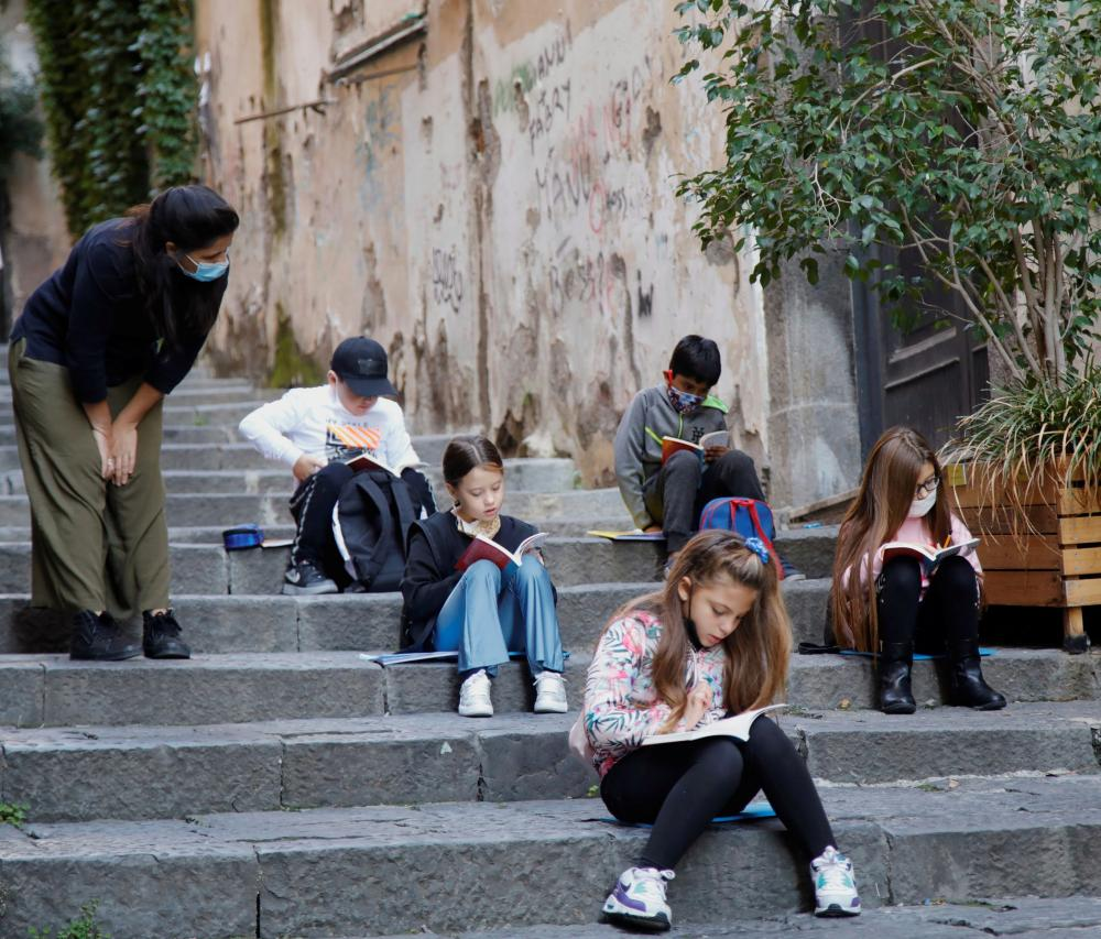 Naples school teacher Pamela Buda holds her lessons to her social distancing students on public steps, after the region of Campania closed schools due to a spread of the coronavirus.