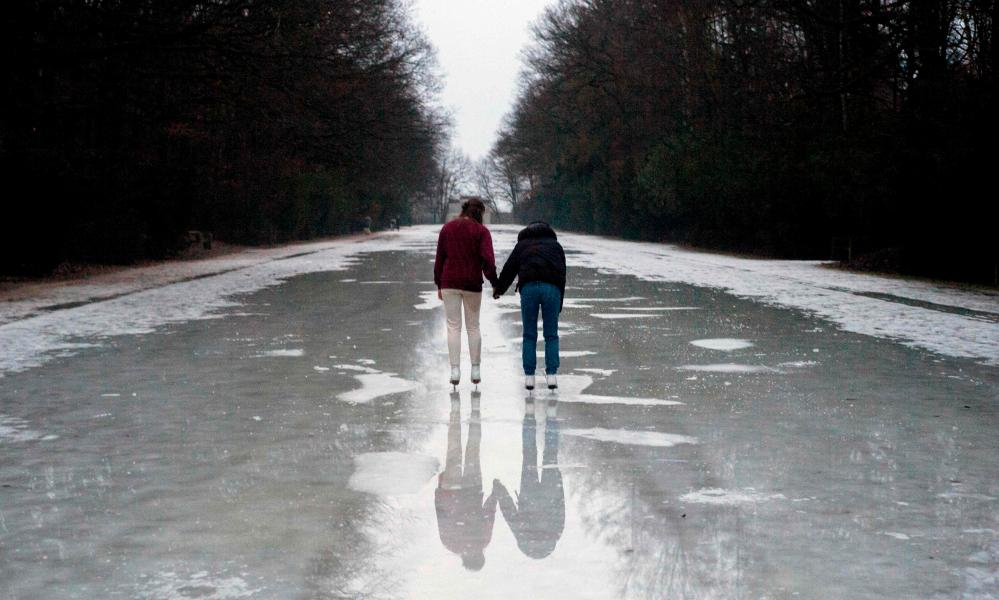 People skate on a ice-covered park path in Prague this week.