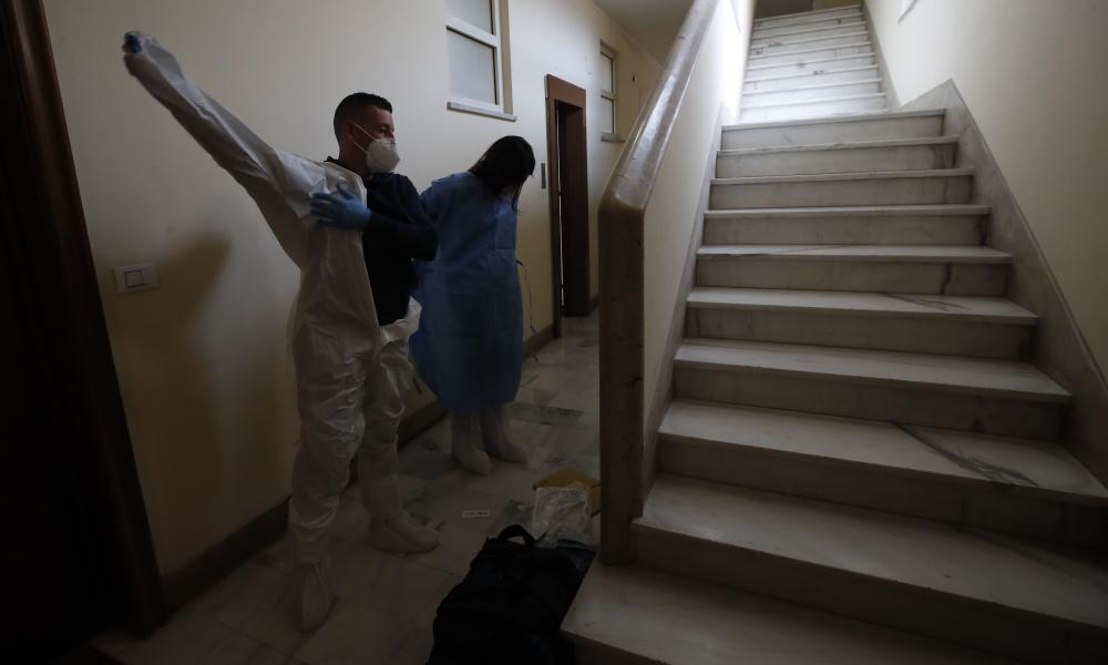 Doctor Elisa Riccitelli, right, and nurse Nurse Luigi Lauri wear protective gear before entering in the home of an elderly Rome resident.