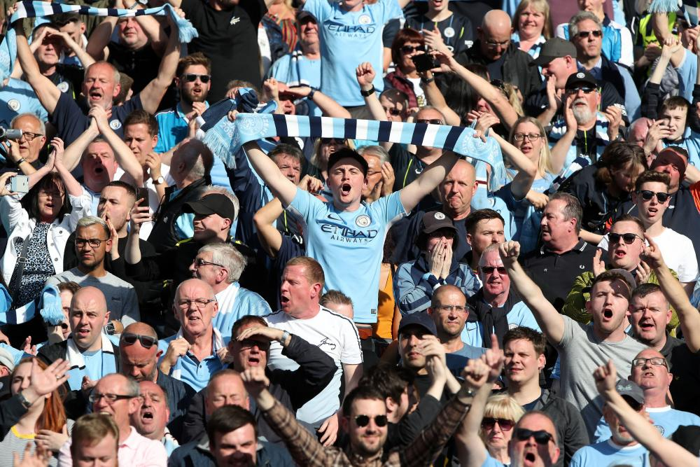 Manchester City fans celebrate as their team are crowned Premier League champions.