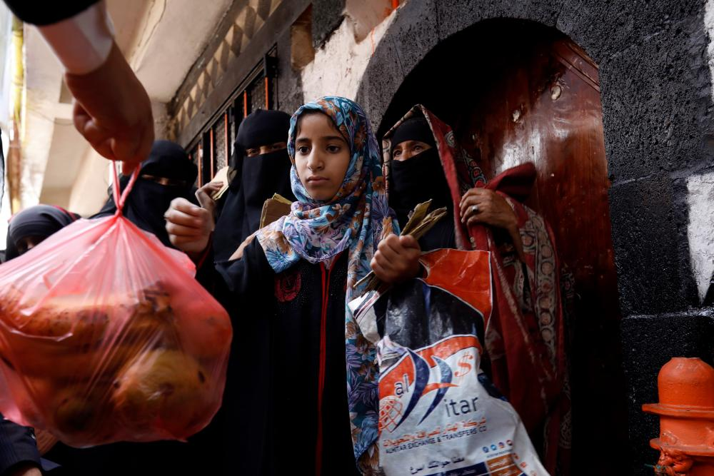 A Yemeni girl gets a free food ration from a charity group in Sana'a.