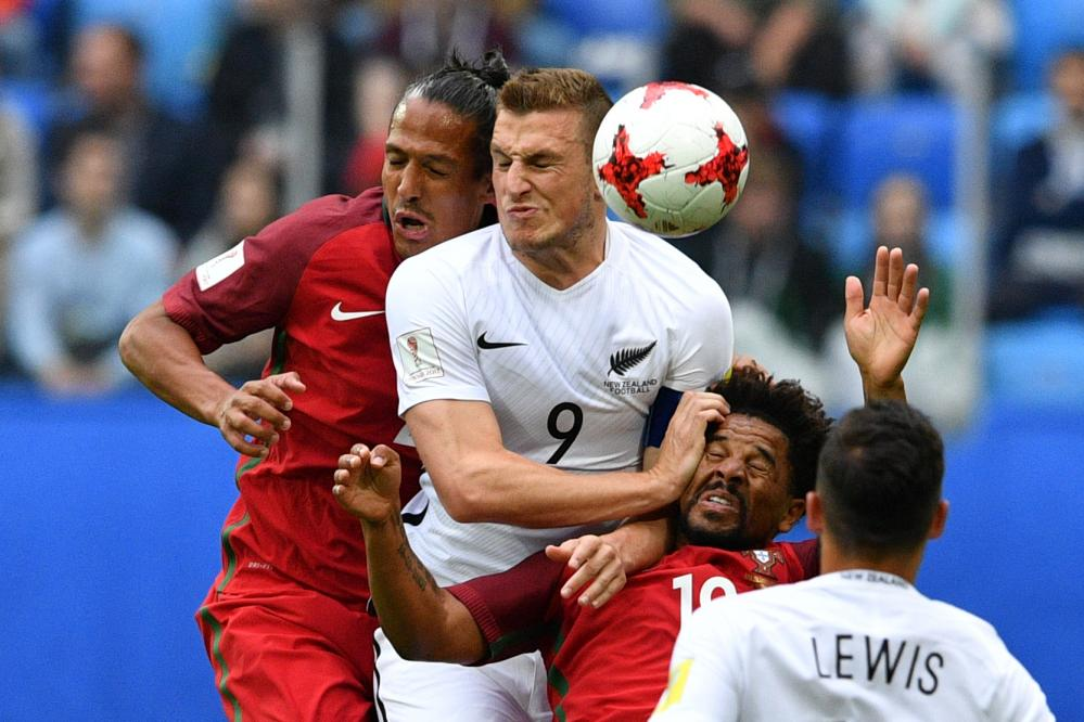 Portugal's Bruno Alves, left, and Portugal's Eliseu, second right, are both beaten to the ball by New Zealandforward Chris Wood.
