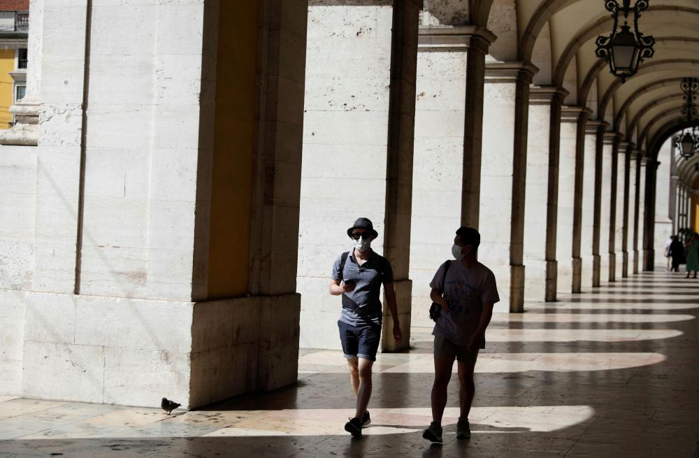 Tourists wearing protective masks walk at Comercio Square, amid the outbreak of coronavirus, in downtown Lisbon, Portugal on 1 September 2020.