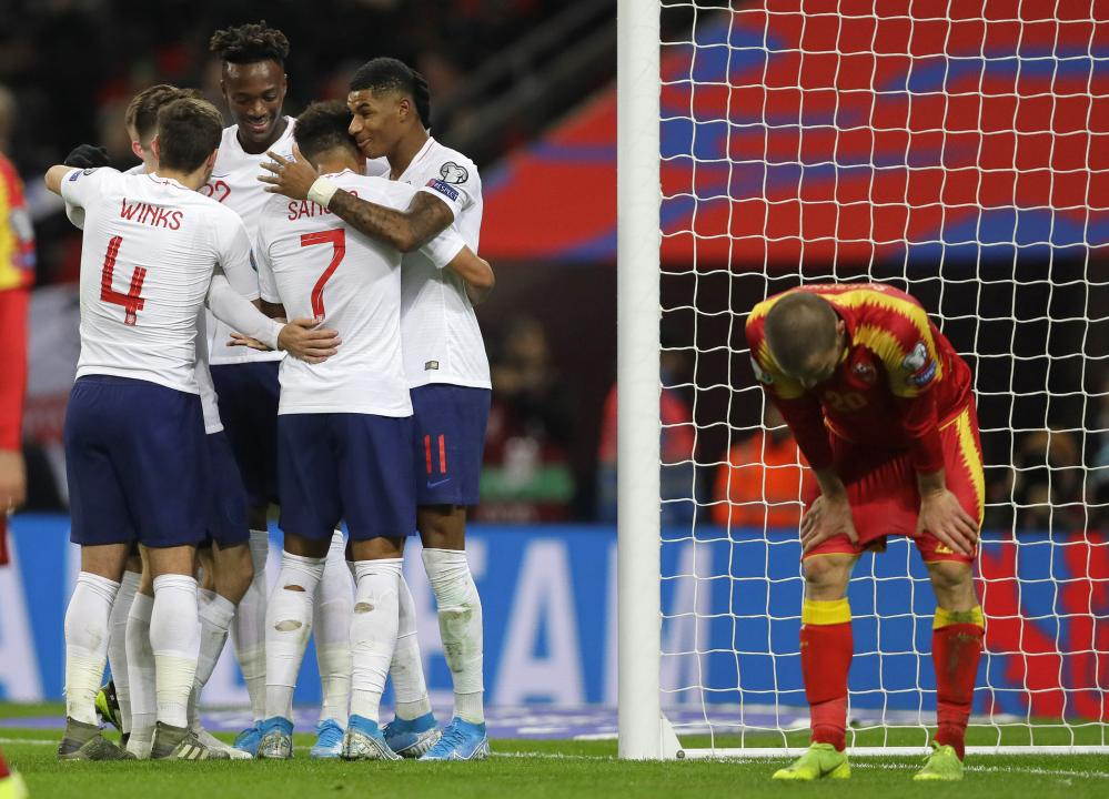 England players celebrate after Montenegro's Aleksandar Sofranac, right, scored an own goal.