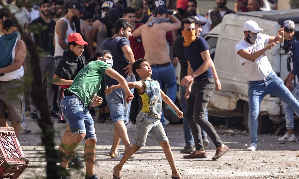 Lebanese anti-government protesters hurl rocks at soldiers amid clashes in the Bab al-Tabbaneh neighbourhood in the northern port city of Tripoli, on June 13, 2020, on the third consecutive day of angry demonstrations across the country due to a deepening economic crisis. (Photo by FATHI AL-MASRI/AFP via Getty Images)