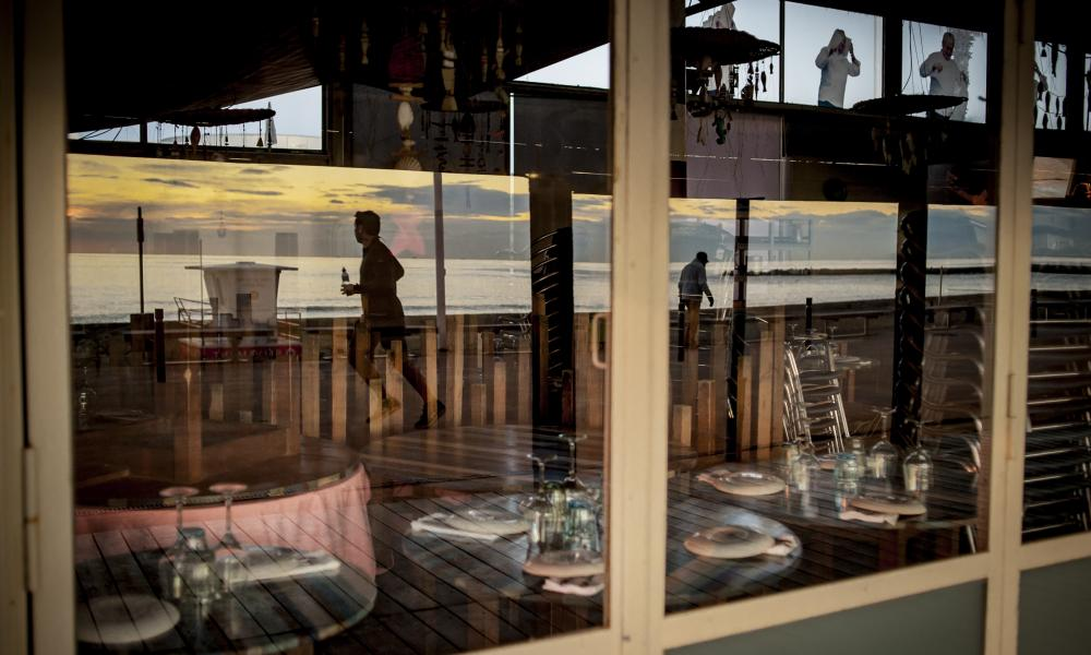 People jogging are reflected on the window of a closed reastaurant early in the morning in Barcelona's maritime promenade. Due coronavirus restrictions bars and restaurants can only open during concrete time slots. Pandemic Daily Life Barcelona Spain - 01 Feb 2021
