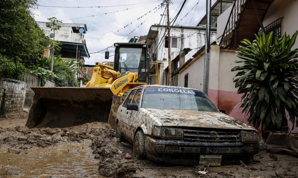 A car is buried in the mud after heavy rain hits Macarao parish in Caracas, Venezuela.
