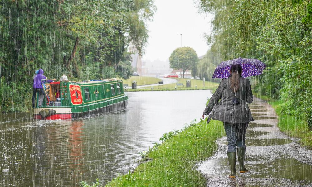 A woman in wellies shelters under umbrella walking on towpath alongside narrowboat in heavy UK rain