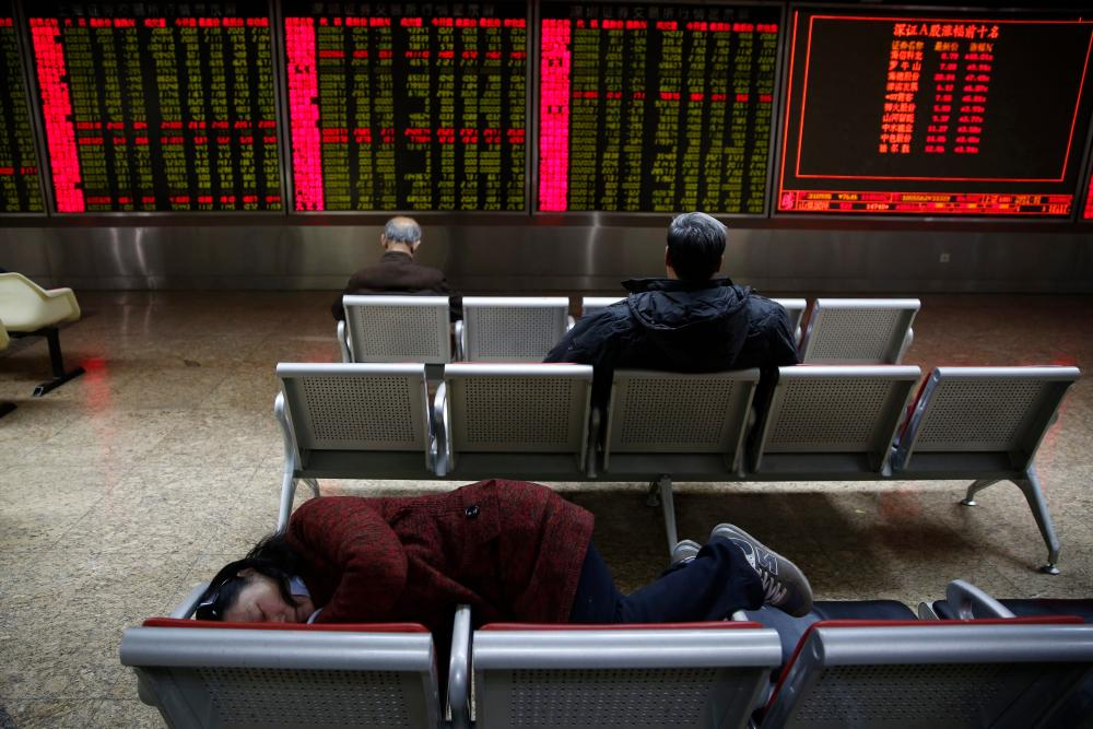 An investor takes a nap in front of an electronic board showing the stock prices at a securities brokerage house in Beijing, China, today.