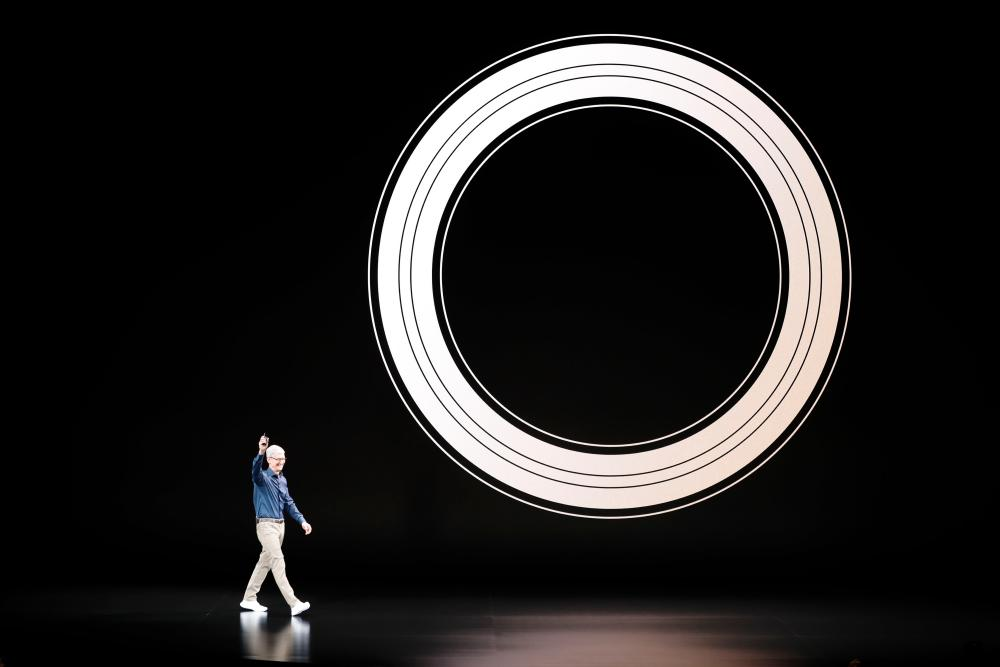 Tim Cook arrives on stage, dwarfed by a huge graphic.