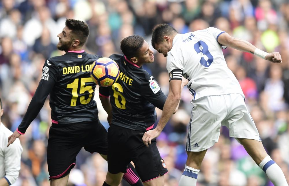 Real Madrid's Pepe heads under pressure from Espanyol's Oscar Duarte and David Lopez.