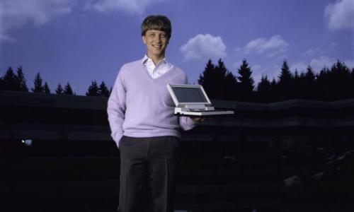 Bill Gates poses outdoors with Microsoft's first laptop in 1986