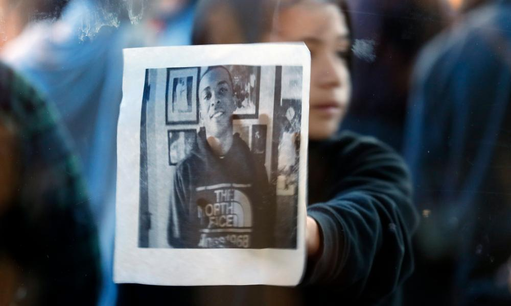 A child holds up a picture of Stephon Clark during a protest.