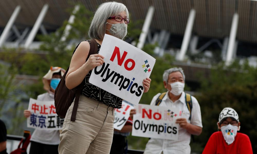 A demonstrator wearing a face mask holds a sign to protest against the Tokyo 2020 Olympic Games a year before the start of the summer games that have been postponed to 2021 due to the coronavirus outbreak, near Japan's National Stadium on Friday.