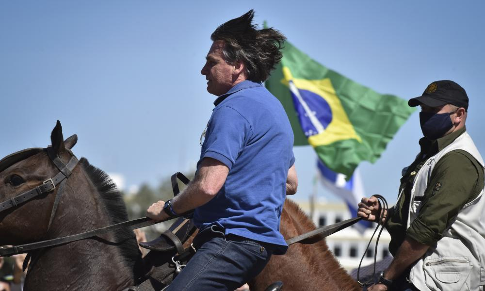 Brazil's President Jair Bolsonaro rides a horse greeting supporters outside the presidential palace in Brasilia on Sunday.