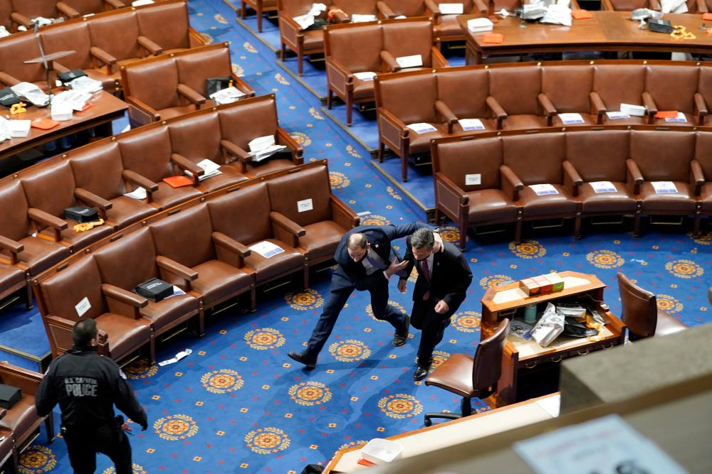 Members of congress run for cover as protesters try to enter the House Chamber during a joint session of Congress.