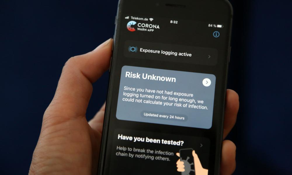 A phone user looks at the English version of the German federal health ministry's Corona-Warn-App