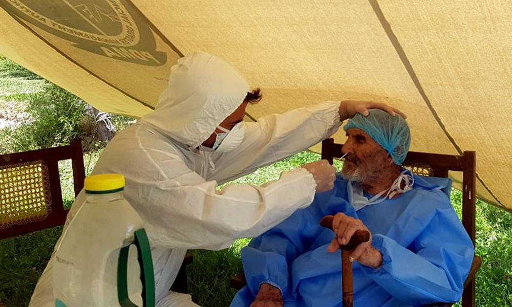 A paramedic wearing protective gear takes a nasal swab of 103 year-old Abdul Alim, to be tested for Covid-19, at the Aga Khan Health Services Emergency Response Centre in Booni, Chitral, Pakistan.