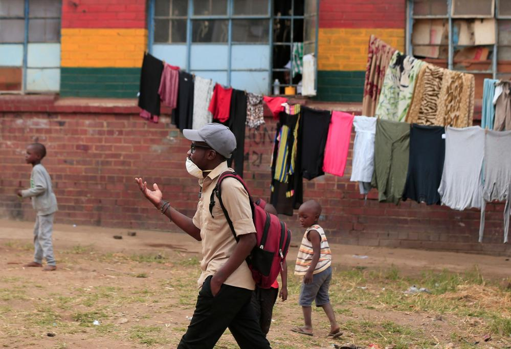 A man wearing a face mask walks in a suburb in Harare, Zimbabwe, on Monday