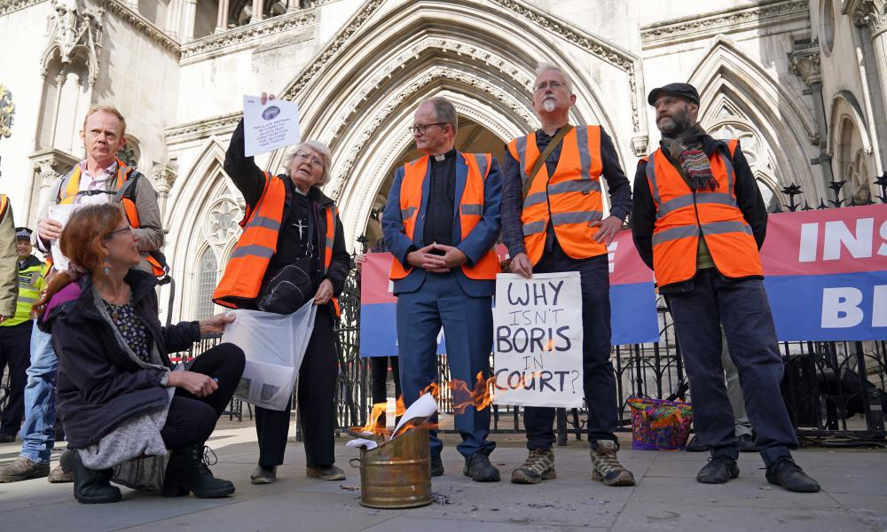 Demonstrators from Insulate Britain burn pages from injunctions on Tuesday outside the high court, central London.