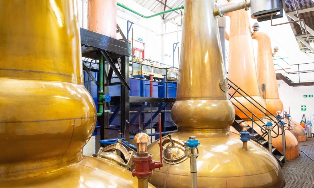 Copper sprit stills at Tobermory whisky distillery, Tobermory, Isle of Bute, Inner Hebrides, Argyll and Bute, Scotland, United Kingdom