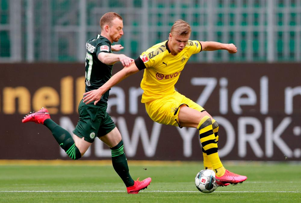 Dortmund's wunderkind Erling Braut Haaland controls the ball as to Wolfsburg's Maximilian Arnoldlooks on.