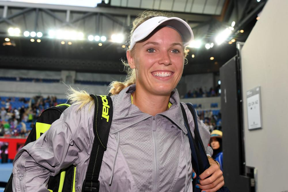 A happy Caroline Wozniacki heads back to the dressing room after beating Mihaela Buzarnescu.