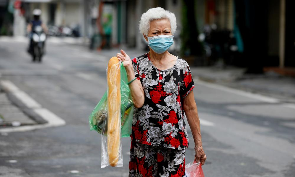 A woman carrying a baguette in Hanoi