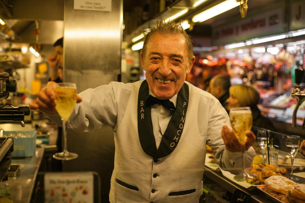 Bartender Juanito holding two cava glasses in the Boqueria Market in Barcelona