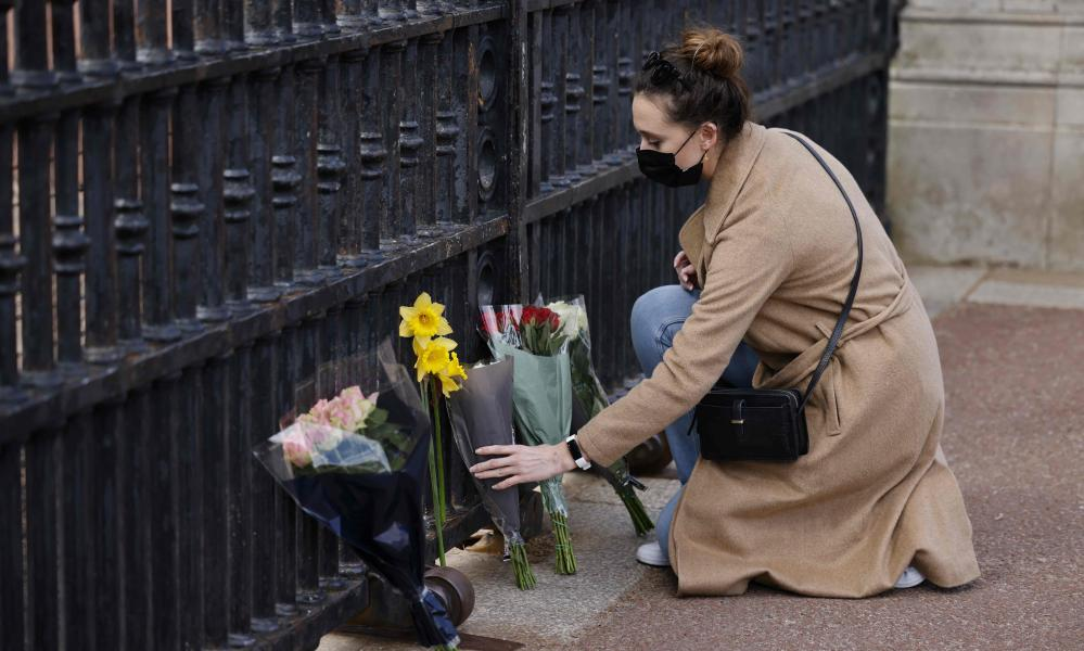 A woman lays a bunch of flowers at the gates of Buckingham Palace after the announcement of the death of Prince Philip