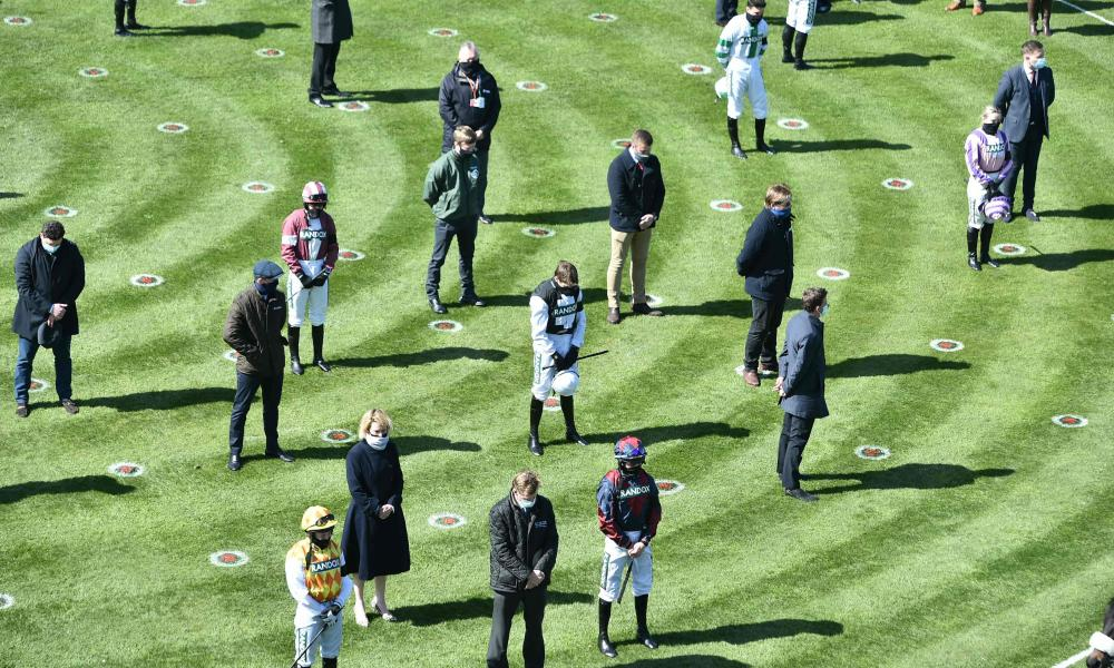 Jockeys and trainers stand for a minute's silence at the Grand National festival at Aintree racecourse in Liverpool.
