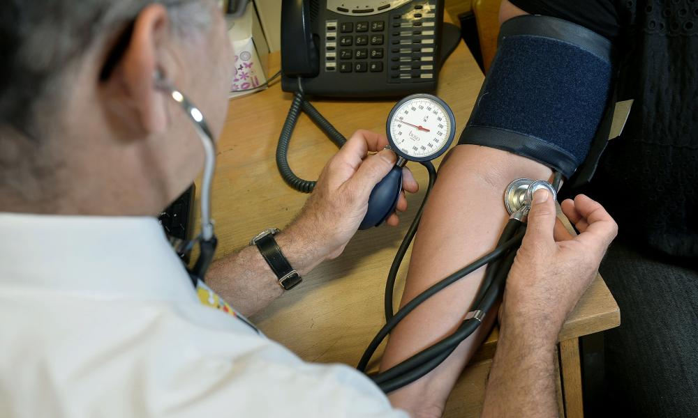 A doctor measures the pulse of a patient