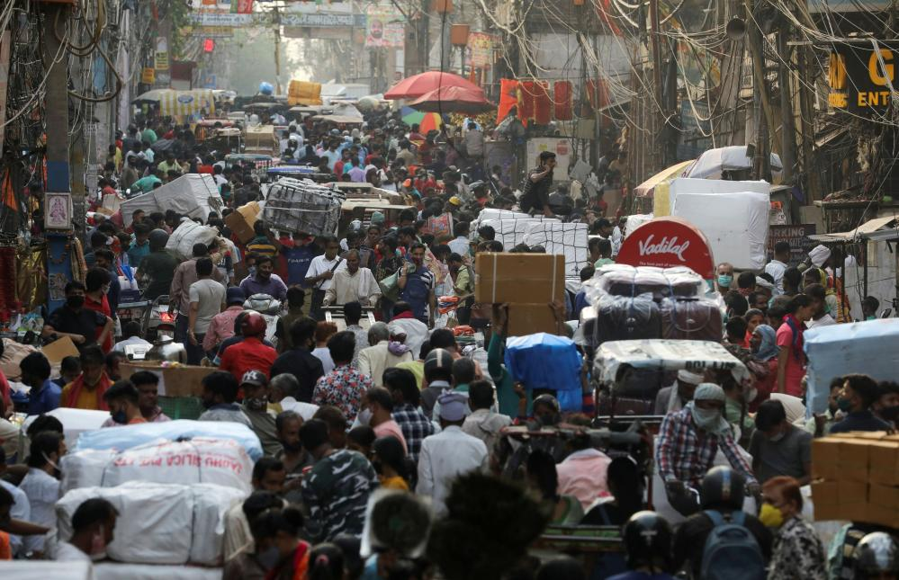 People walk at a crowded market amidst the spread of the coronavirus disease in the old quarters of Delhi, India, on 6 April, 2021.