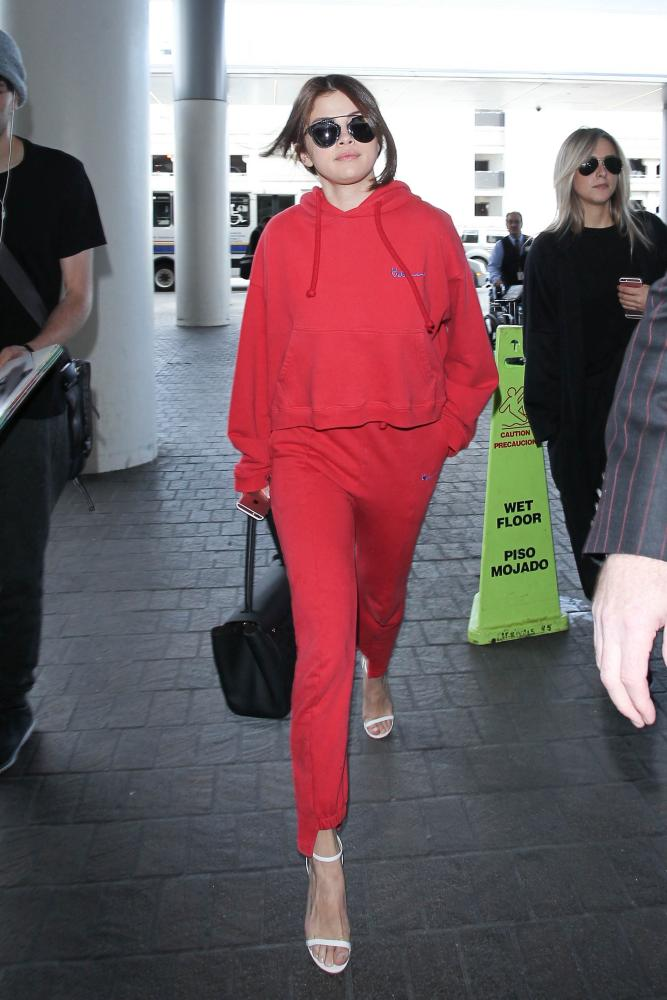 Selena Gomez at LAX in a Vetements hoodie and matching tracksuit bottoms.