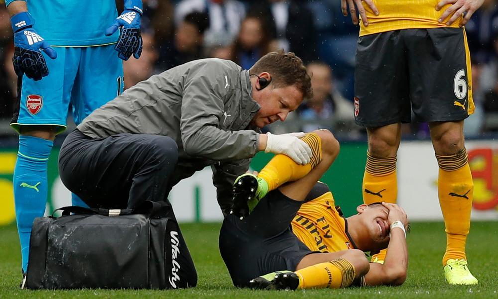 A grimacing Alexis Sanchez receives medical attention.