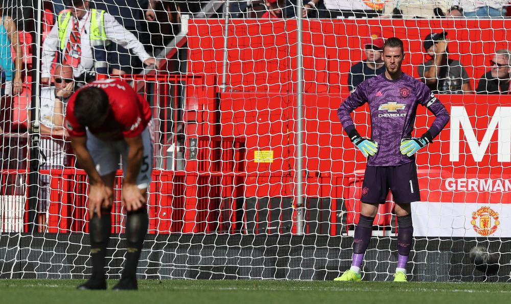David de Gea and Harry Maguire react to conceding a late goal to Patrick van Aanholt.