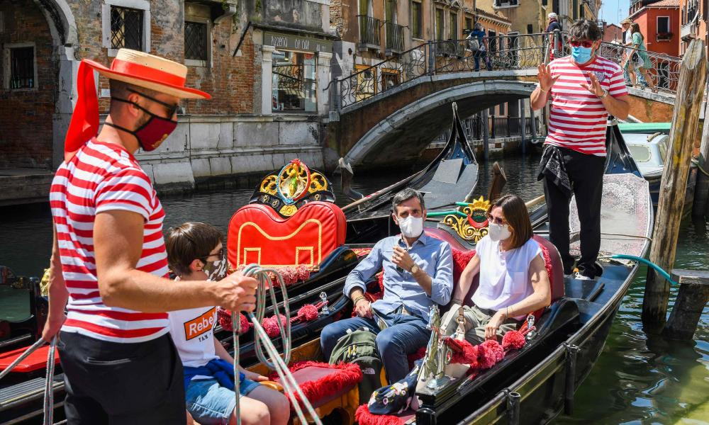Gondoliers take customers for a gondola ride on a canal in Venice as Italy eases its lockdown restrictions.